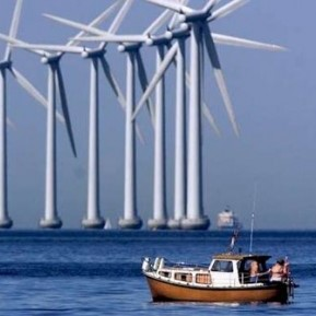 wind turbines in sea with boat in foreground